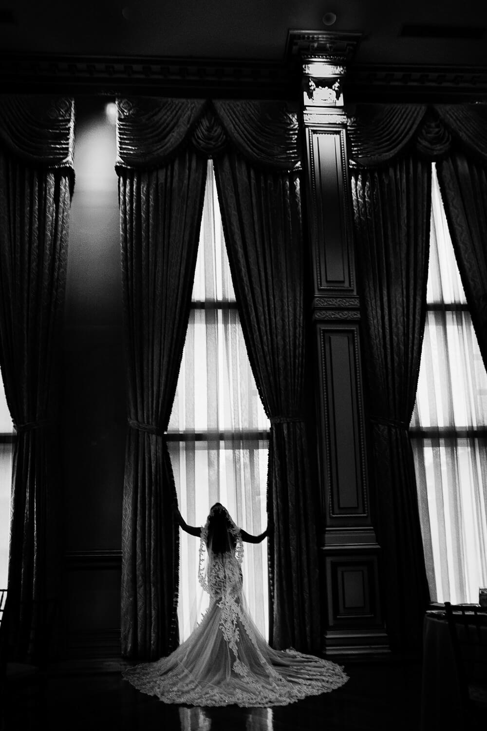 Silhouette of a Bride in front of the window in the grand ballroom at the Tides Estates New Jersey Wedding Photographer