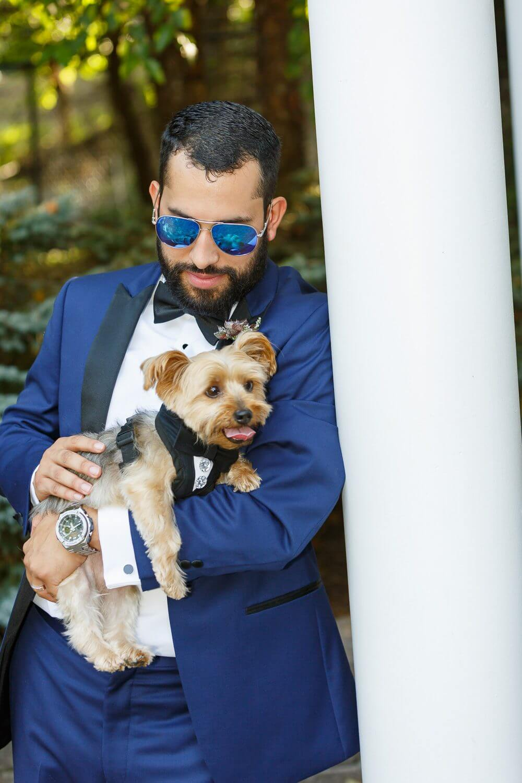 Groom holding Ring bearer dog at the Tides Estates New Jersey Wedding Photographer