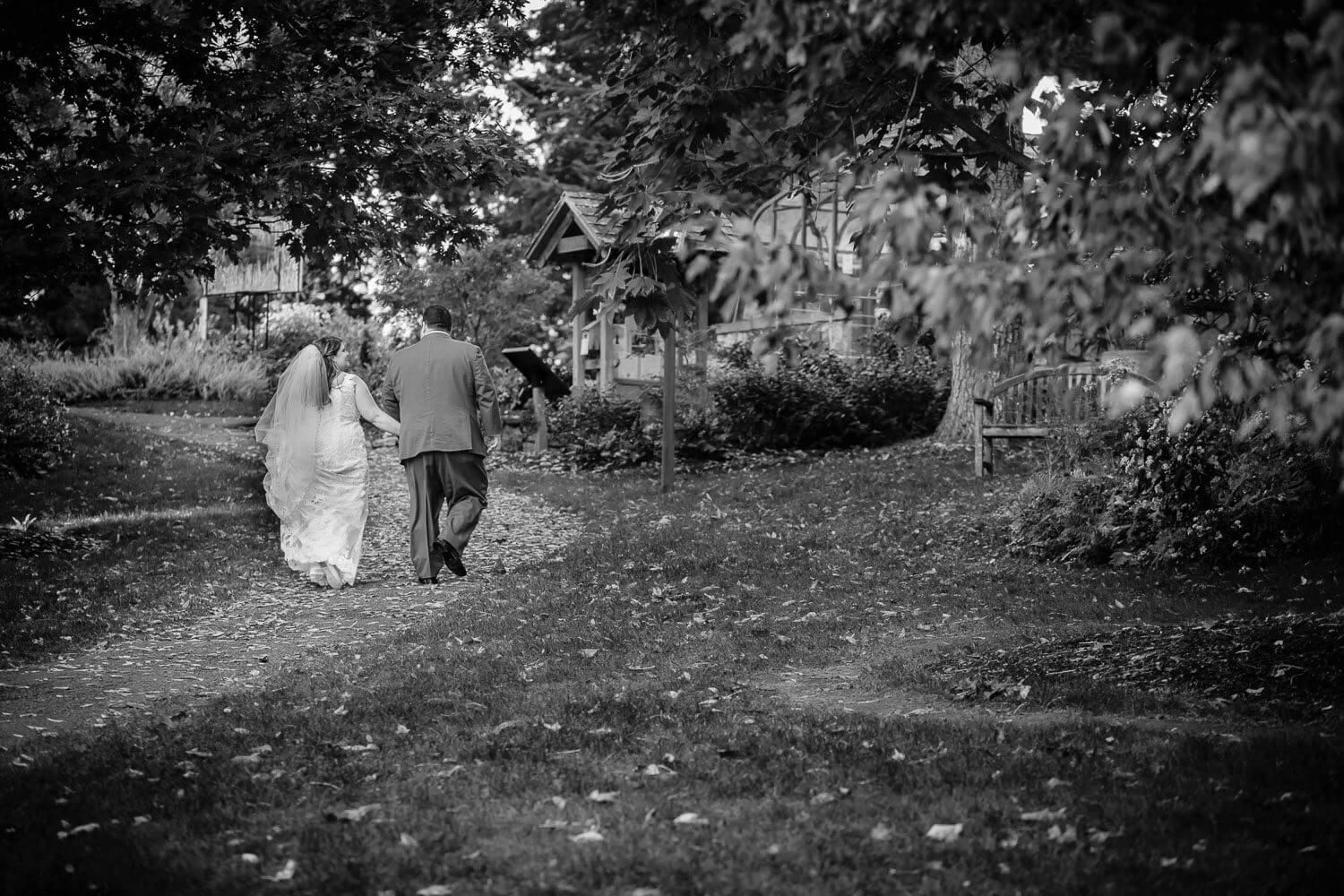 Bride and groom walking away in black and white at Jockey Hollow Park New Jersey Wedding Photography