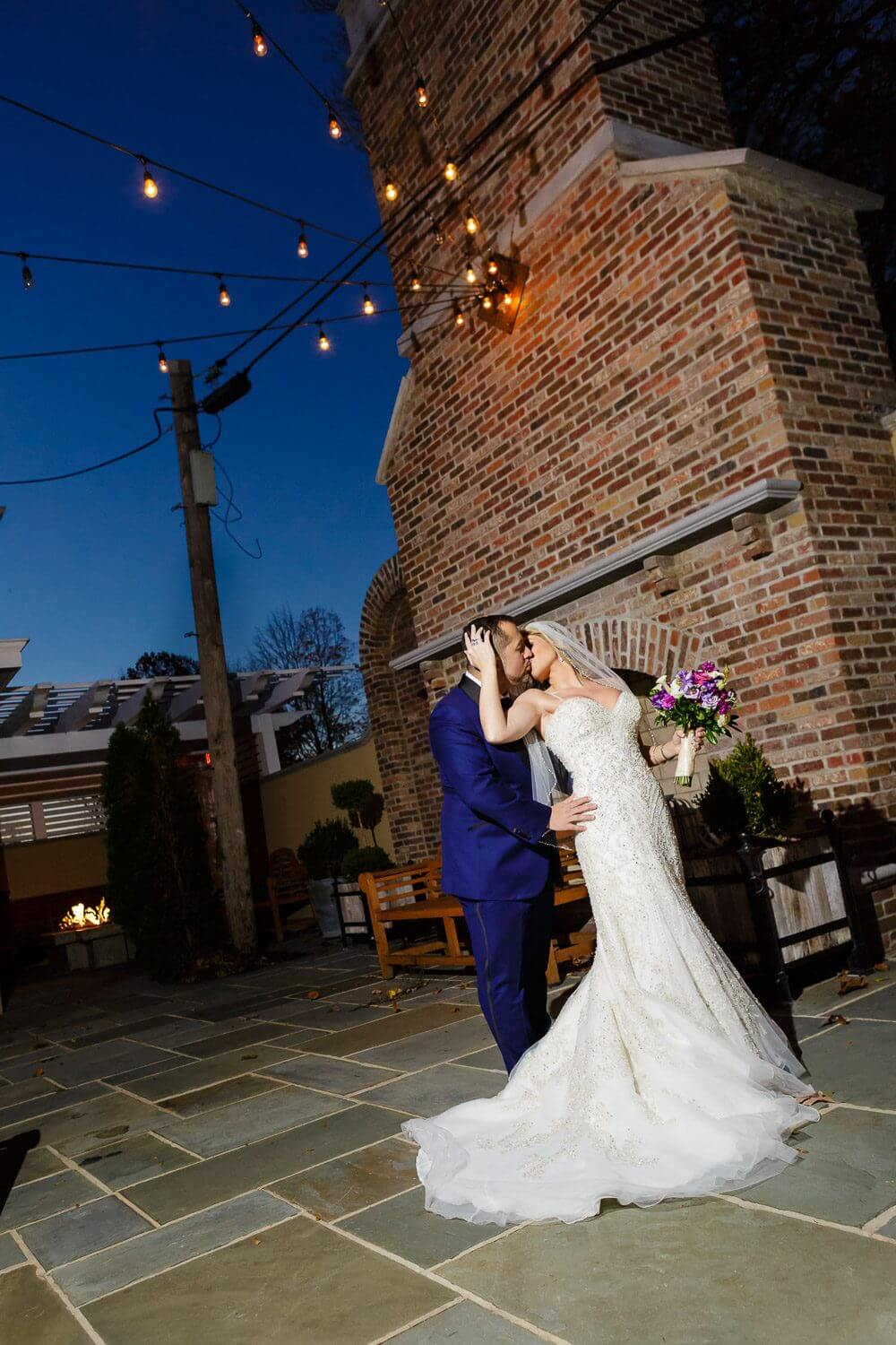 Bride and Groom kissing under the string light at the ryland incc New Jersey Wedding Photography