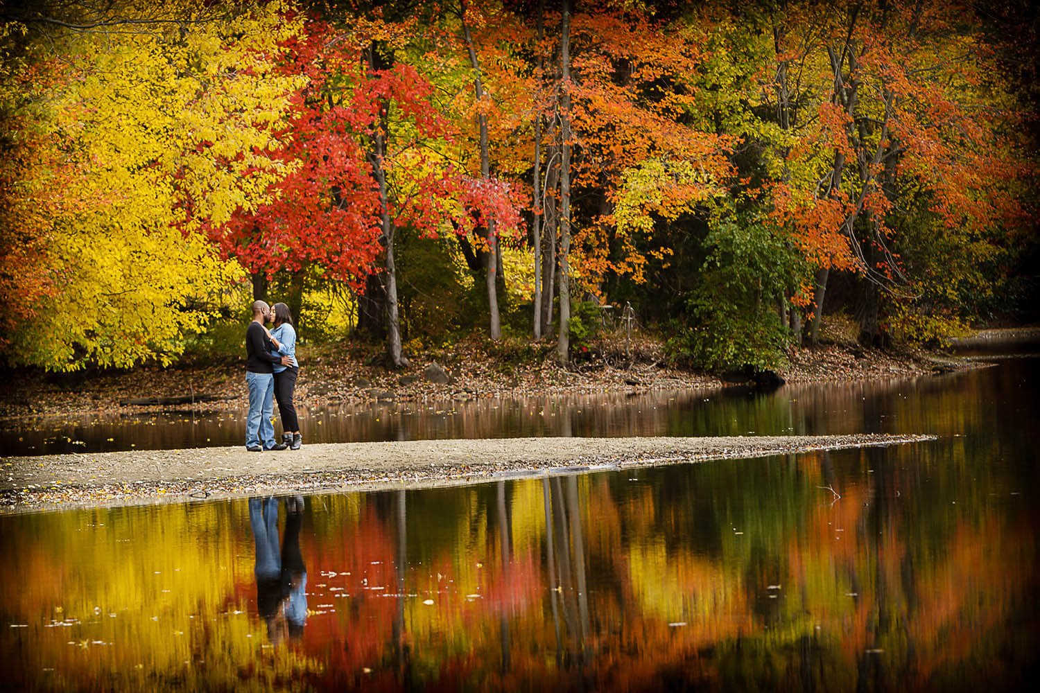 New Jersey engagement photo of a couple at a pond in ramapo reservation in the fall
