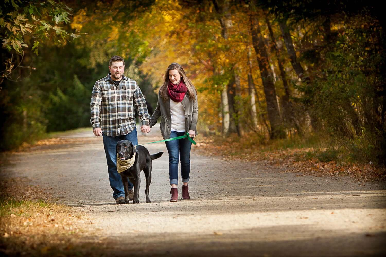 New Jersey engagement photo of a couple walking with their large black dog on a country road in the fall