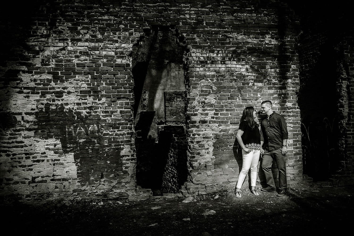 New Jersey engagement photo of a couple in black and white against an old wall