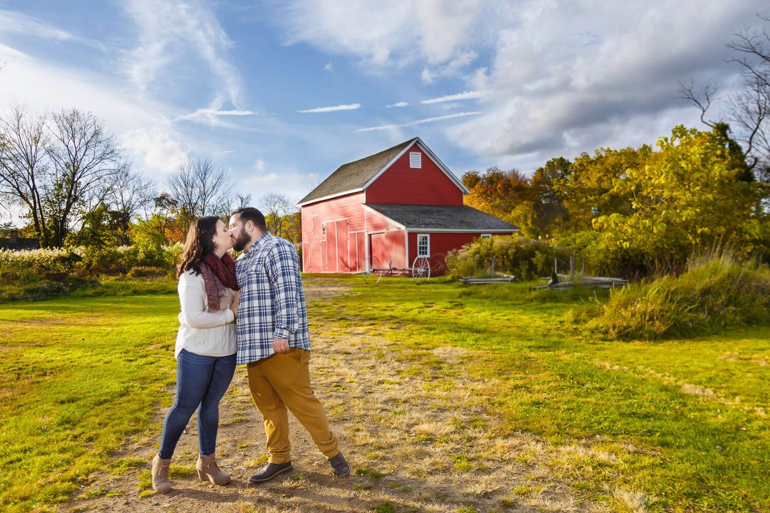New Jersey engagement photo of a couple kissing in front of red barn