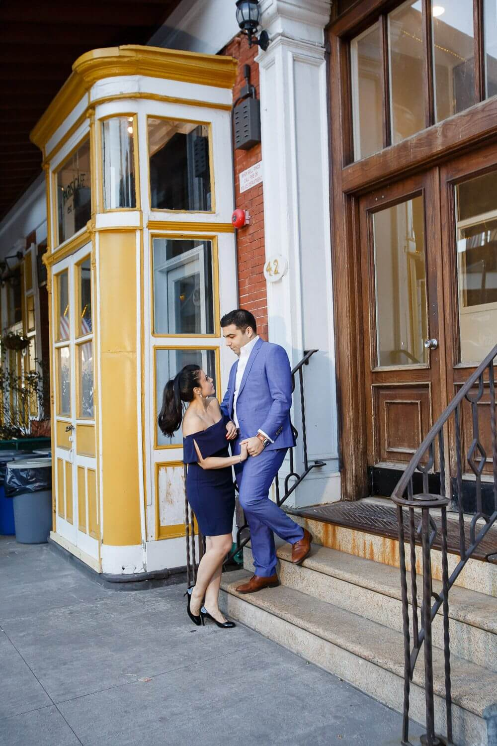 New Jersey engagement photo of a couple looking at each other on the stairs in South street seaport