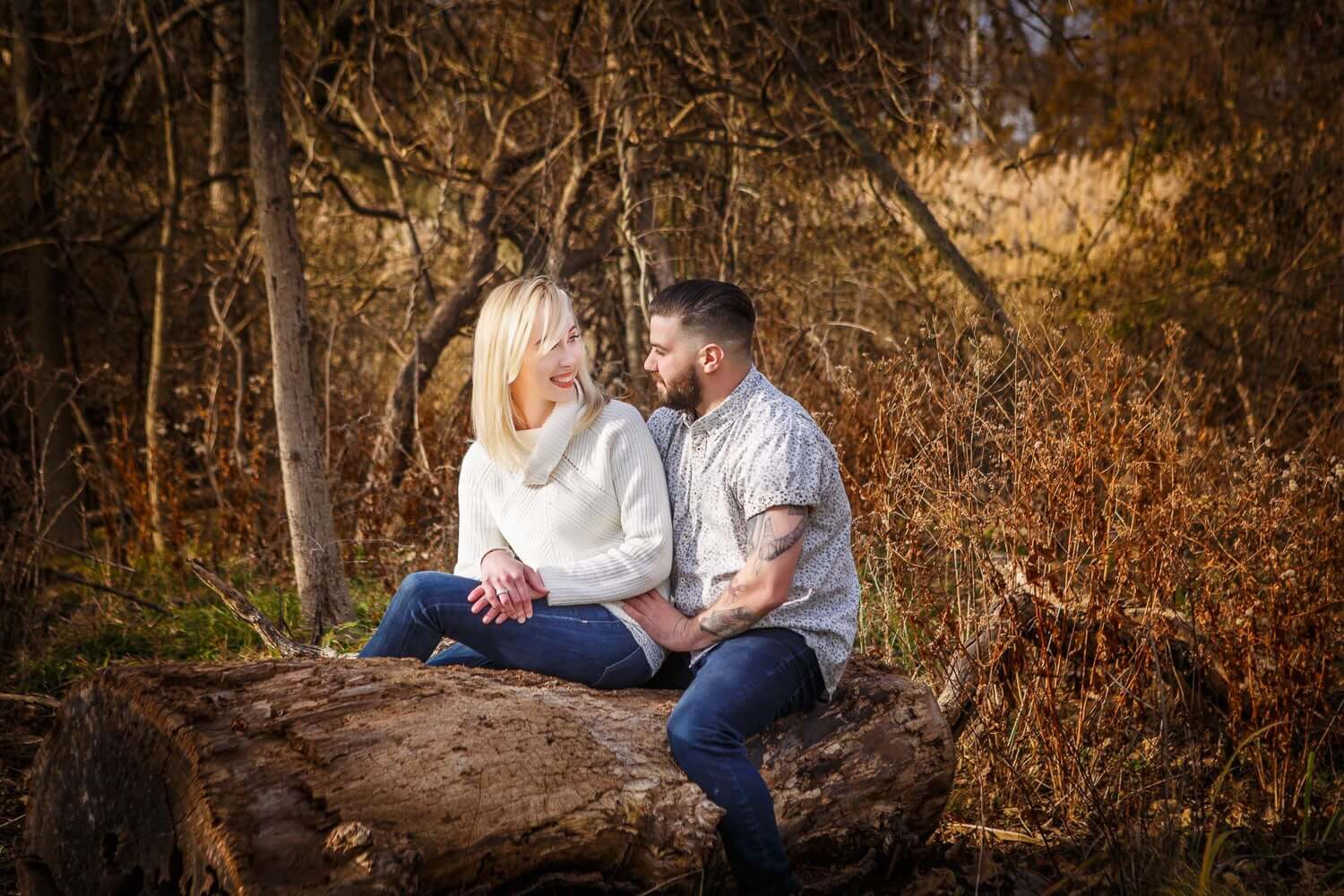 New Jersey engagement photo of a couple sitting on tree stump