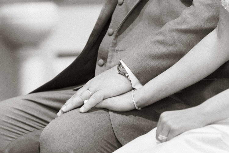 Grooms guide a sensitive moment holding brides hand in church