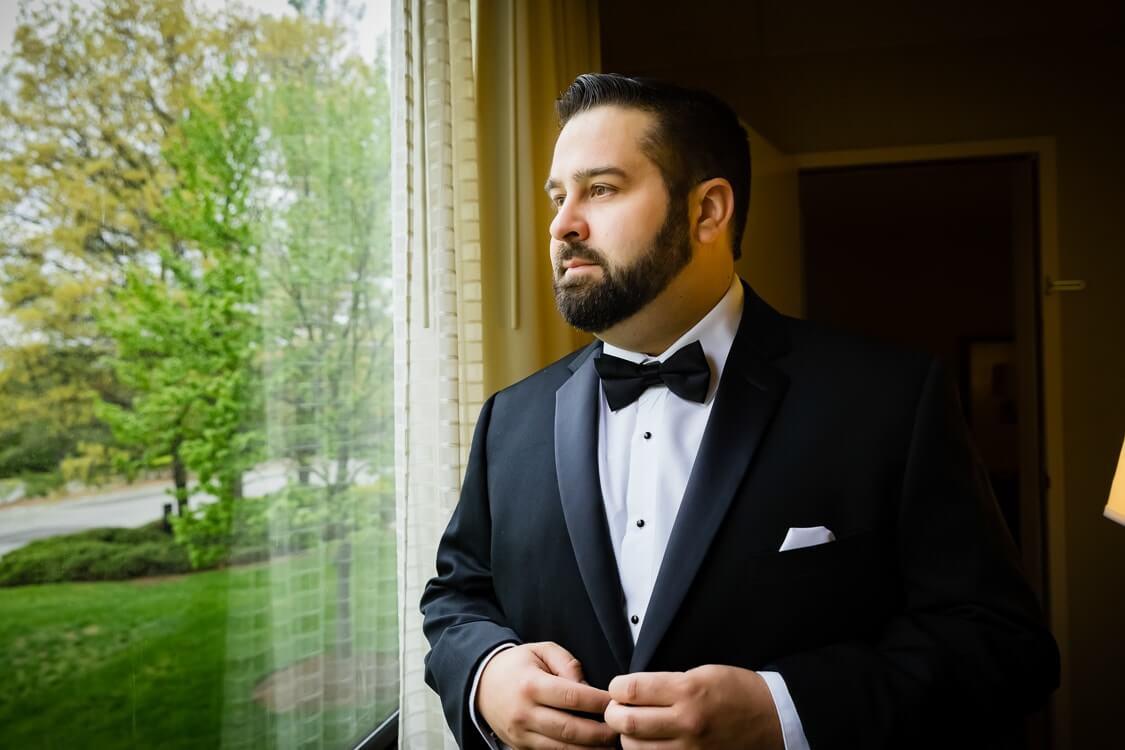 Groom's guide groom looking out window in color